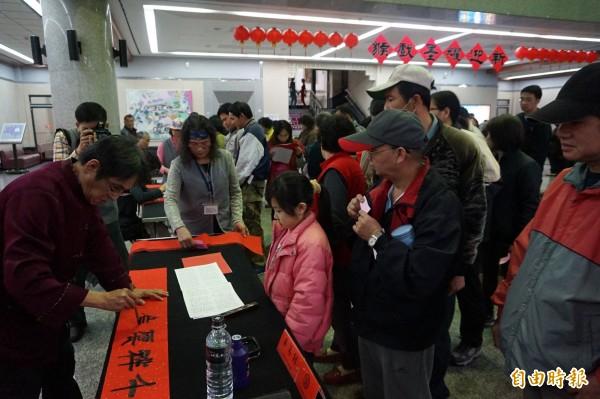 台中市港區藝術中心舉辦名家揮毫,吸引民眾排隊免費索取。(記者歐素美攝)