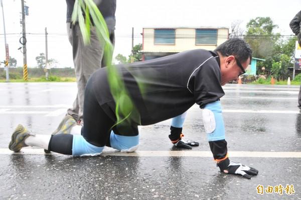 偽皮鞭催促下,賴坤成冒雨賣力爬爬爬,忍不住抱怨「為什麼馬路上這麼多碎石頭」、「手套太薄了」!(記者花孟璟攝)