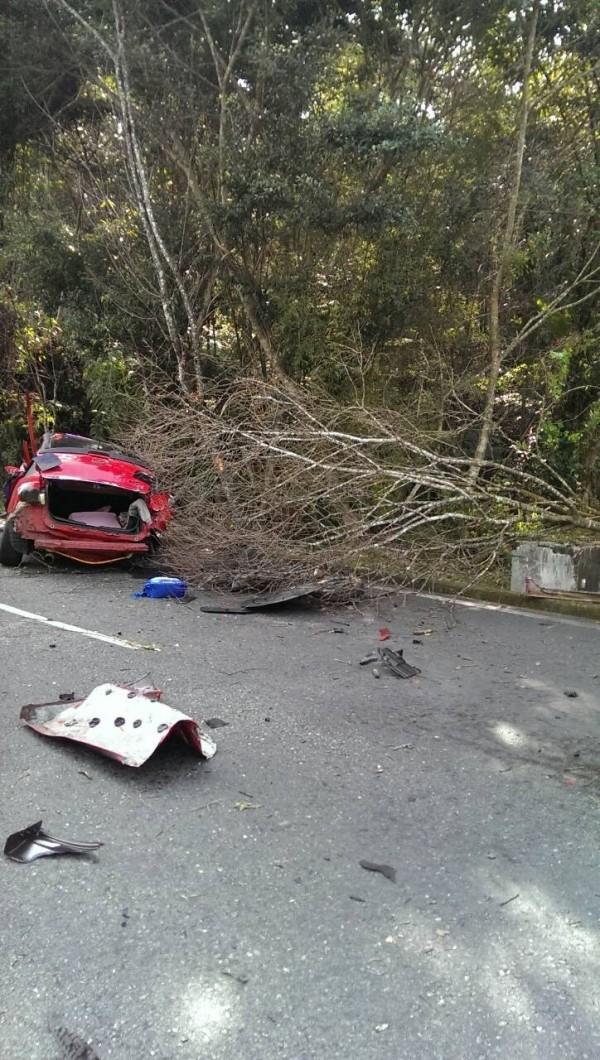 一輛紅色轎車在日月潭中潭公路自撞路樹,造成一死一重傷,整輛車嚴重變形,零件散落一地。(記者劉濱銓翻攝)