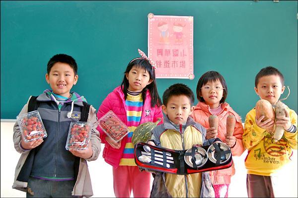興華國小學童拿著自家種植的紅蘿蔔等蔬果義賣,捐助雲林家扶。(記者鄭旭凱攝)