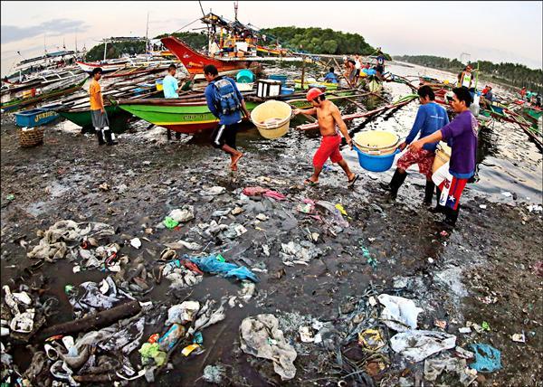 19日在世界經濟論壇開幕日發布的報告警告,2050年時,海洋中的塑膠可能會比魚還多。圖為菲律賓馬尼拉南方帕拉納克市(Paranaque)的漁村漁民卸下漁獲,海灘上處處可見垃圾。(歐新社)