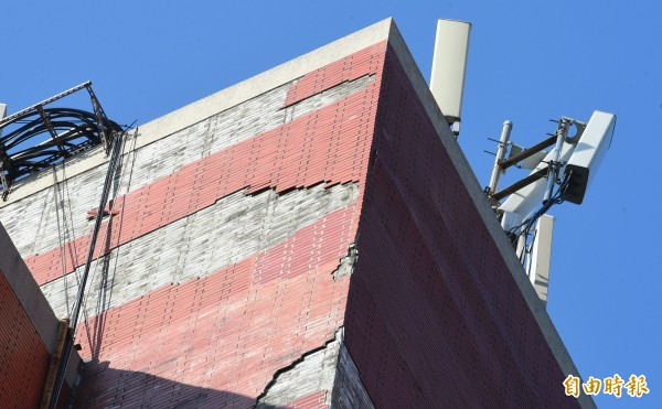 寒流襲台後,立院的群賢樓外牆有大片磁磚剝落,現場警衛早已拉起封鎖線,就怕會砸到路過的人。(記者張嘉明攝)