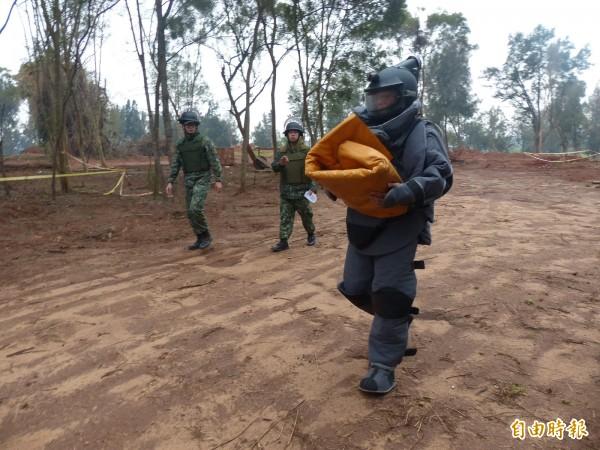 金防部未爆彈處理小組將未爆彈包在防爆毯裡移走。(記者吳正庭攝)