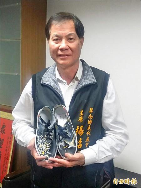 卑南鄉代會主席楊招信見學生用心畫的鞋子,立即以一萬元認購。(記者王秀亭攝)