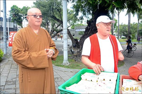 寶積學舍證守法師(左)與葉姓身障志工最近在屏東市中山公園發送便當。(記者葉永騫攝)