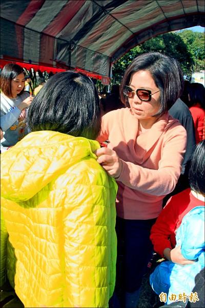 于美人(右)抵達會場立即化身超級媽咪,手腳俐落地為小朋友挑選適合身材與喜歡顏色的羽絨衣。(記者佟振國攝)