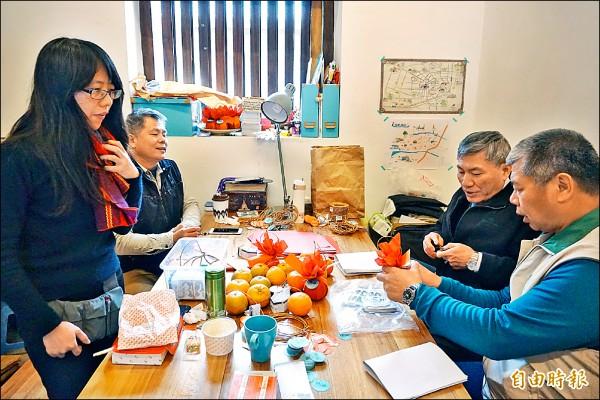 台中市副市長張光瑤(右二)及市議員蕭隆澤(右一)到摘星山莊,對摘星青年李雅萍(左一)包裝的桶柑等創作興味盎然。(記者歐素美攝)