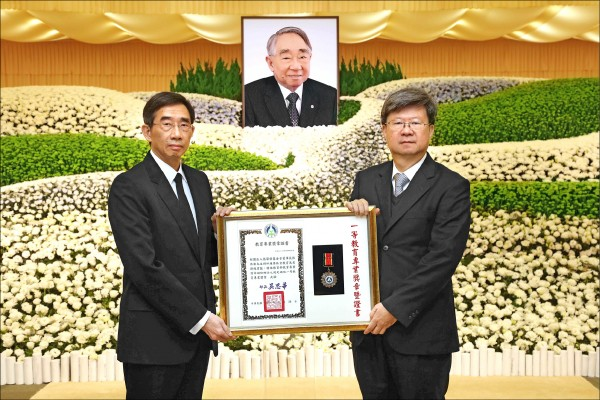 教育部長吳思華(右)昨前往其追思會堂致意,並追贈教育部最高榮譽「一等教育專業獎章」,由家屬代表張國華(左)受獎。(張榮發基金會提供)