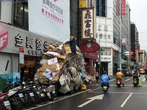 有網友在臉書爆料,指出位於台北市重慶南路上,有一台資源回收車上疊了相當於一層樓高的回收物品。(圖片取自「爆料公社」臉書)