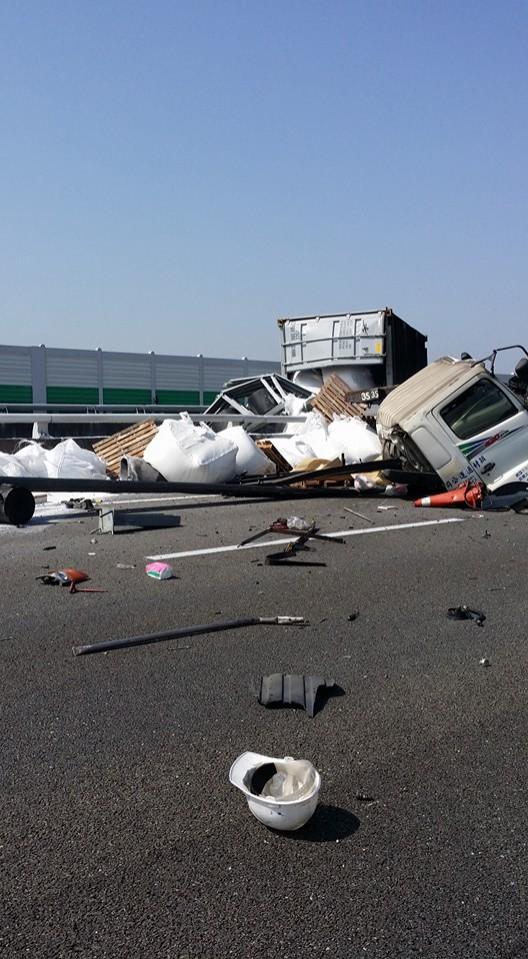 貨櫃車在國道3號南投交流道前發生自撞,嚴重撞擊力道導致車頭與貨櫃、拖板分家,車體零件散落一地。(取自臉書「爆料公社」)