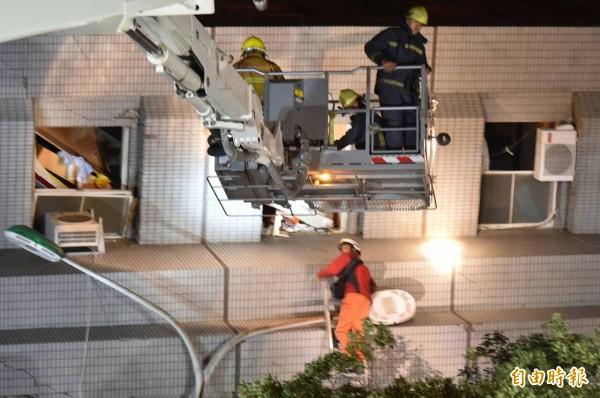 救災人員搭雲梯車營救受困民眾。(記者張忠義攝)