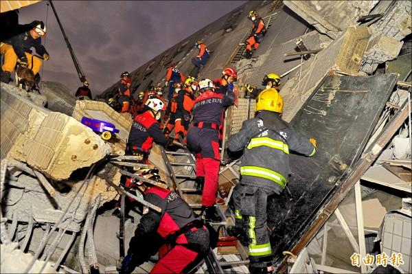 搜救人員爬進廢墟中,尋找任何可能生還者。(記者王捷攝)