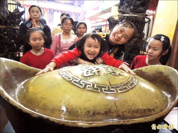 台中廣天宮 財神廟的大元寶 ,吸引信徒摸金元 寶求財運。 (記者蔡淑媛攝)