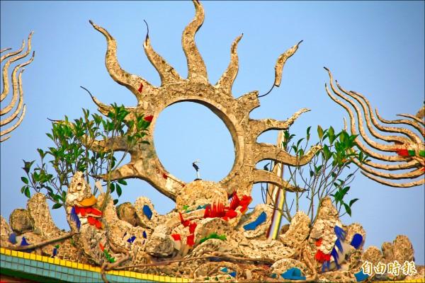 慈雲寺廟宇並不大,但供奉罕見的 麻糬佛祖,屋頂上的石雕旁,長了兩棵 小榕樹。 (記者林宜樟攝)