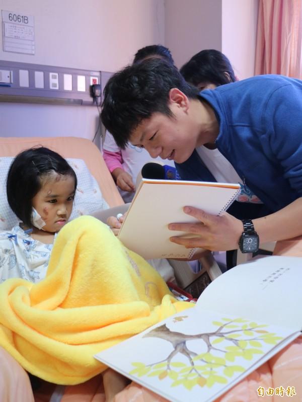 林素琴專注地聽著醫生叔叔念繪本童書。(記者林孟婷攝)