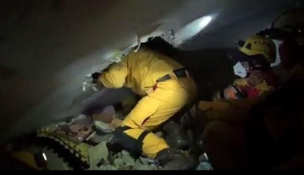 救難人員破壞建物,爬入其中搜索受困災民。(圖擷取自影片)