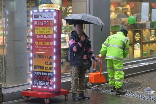 南韓湧入超過15萬5000名中國遊客,但面對首爾禁菸規定,強國遊客卻不願意入境隨俗,大方在街頭違規抽菸。(圖取自《韓國時報》)