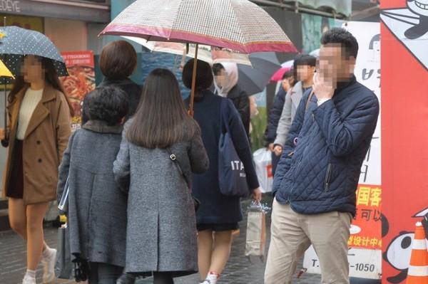面對首爾禁菸規定,強國遊客不僅不甩禁令繼續抽,還從口袋拿出鈔票向規勸者表示,「我有錢,會付罰款」。(圖擷取自《韓國時報》)
