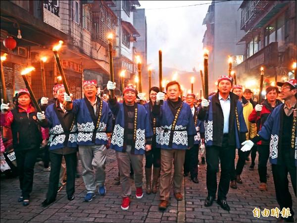 新北市瑞芳火把節昨天下午在寒風中登場,民眾一起舉火把遊街。(記者俞肇福攝)