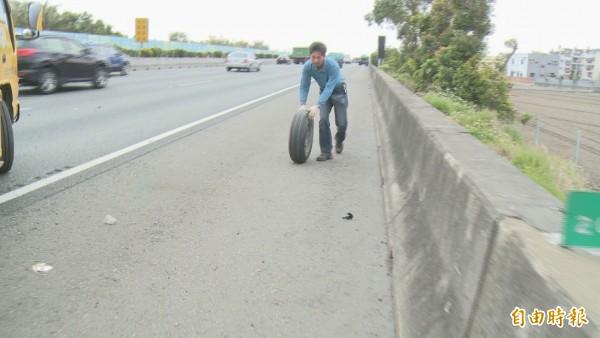 拖吊車業者在高速公路上把彈飛60公尺遠的輪胎滾回。(記者湯世名攝)