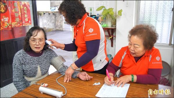 土城裕生里熱心志工細心為長輩量體溫、血壓,並一一做紀錄,貼心服務讓里內長輩都讚不絕口。(記者張安蕎攝)