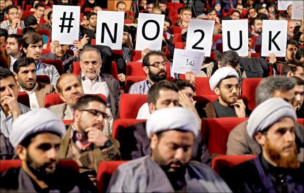 伊朗史上首度國會與專家會議共同大選廿六日登場,這場大選將決定溫和派總統羅哈尼的改革路線能否持續,也引發保守派與溫和派較勁。圖為保守派支持民眾廿四日在德黑蘭一場造勢場合高舉「對英國說不」的標語,反對英國干預伊朗事務。(路透)