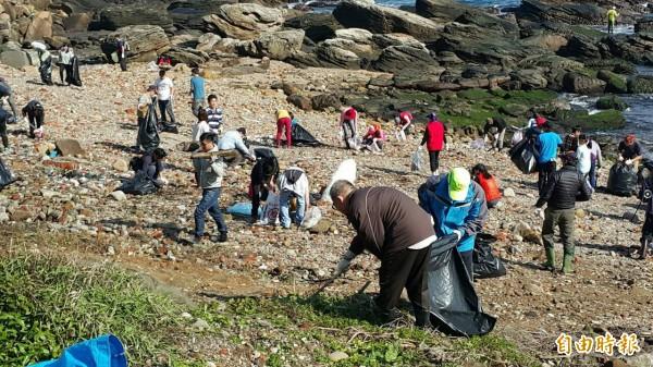 基隆外木山海灘有環保社團發起淨灘活動,民眾頂著久違的陽光撿拾垃圾與海漂物。(記者俞肇福攝)