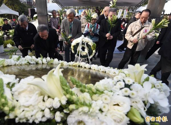 今年為228事件69週年,紀念會28日在台北228和平公園舉行,民眾與受難者家屬在228紀念碑前獻花表達追思。(資料照,記者廖振輝攝)