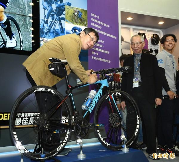 台北市長柯文哲(左)3日出席2016台北國際自行車展,並在他挑戰一日雙城及雙塔的座車上簽名,提供拍賣做公益。(記者方賓照攝)