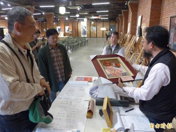 「淡水假日畫市」在淡水文化園區舉行。出價購得畫作者,將其帶回 。(記者李雅雯攝)