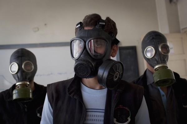 據信IS化武頭子已於上月被捕。圖為志工2013年9月在敘利亞北部阿勒坡示範遭化武攻擊時如何配戴防毒面具。(法新社)