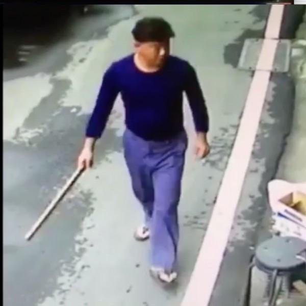 藍衣男子持棍棒欲進入民宅打狗。(翻攝畫面)