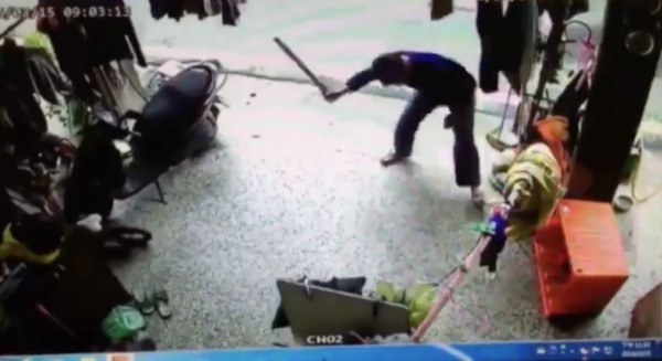 藍衣男子持棍棒進入民宅打狗。(翻攝畫面)