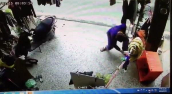 藍衣男子持棍棒進入民宅打狗,朝橘色箱子內的狗打了好幾下。(翻攝畫面)