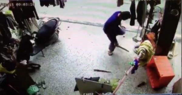 藍衣男子持棍棒朝橘色箱子內的狗打了好幾下,還打到棍子斷掉。(翻攝畫面)