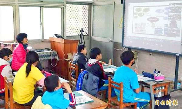 竹山鯉魚國小學童透過網路遠距教學,與外籍老師在課堂上全程以英語互動,校內老師則從旁輔助。(記者謝介裕攝)