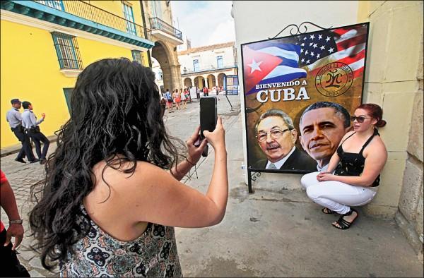 美國總統歐巴馬二十日抵達古巴訪問,古巴首都哈瓦那街頭十九日已出現不少歡迎歐巴馬來訪的標語,圖為一名來自加州的觀光客,與印有歐巴馬和古巴總統勞爾.卡斯楚肖像的海報合影。(路透)
