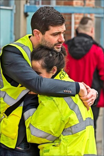 一對男女在布魯塞爾機場發生炸彈攻擊案後互擁安慰。(美聯社)