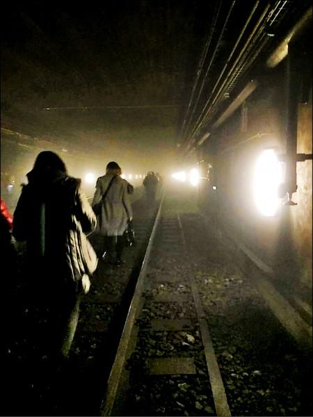 布魯塞爾市區馬爾比克地鐵站發生爆炸後,目擊者拍下當時乘客沿地鐵軌道疏散。(路透)
