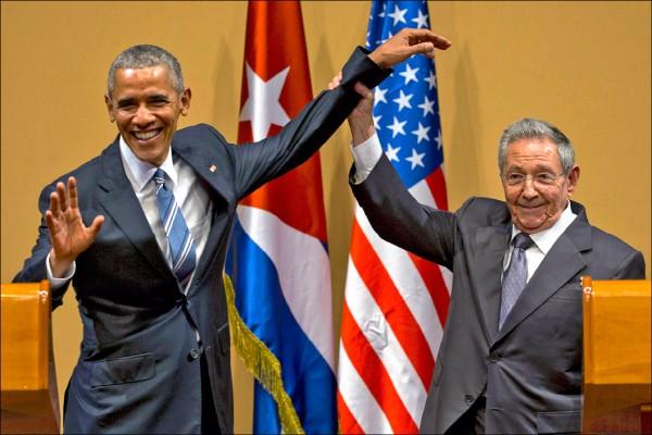 古巴最高領導人勞爾.卡斯楚廿一日在美古元首會後的記者會上,企圖舉起美國總統歐巴馬的手,讓歐巴馬做出握拳向上的左派象徵動作,卻因歐巴馬手腕鬆軟、手掌攤開而告失敗,場面頗為尷尬。(美聯社)