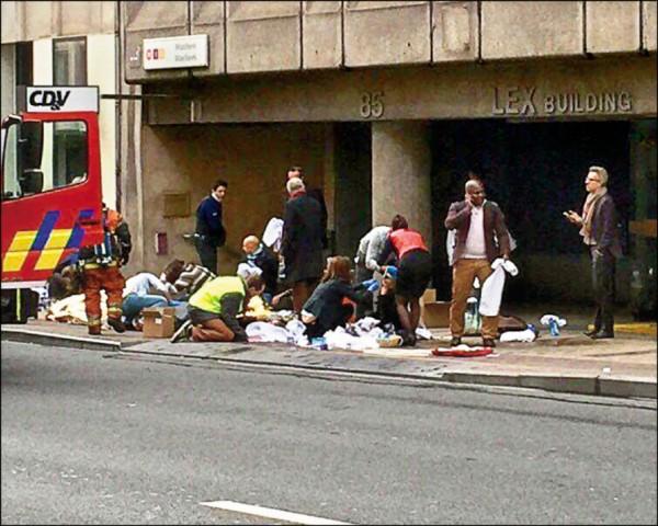 比利時連遭恐攻,布魯塞爾市區靠近歐盟總部的馬爾貝克(Maelbeek)地鐵站,二十二日遭炸彈攻擊,救援人員在地鐵站外照護傷者。(歐新社)