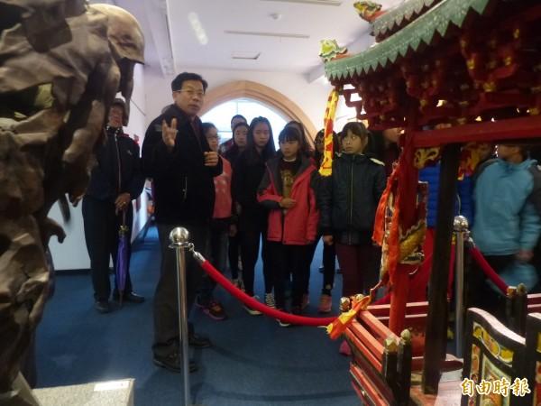 金門縣文化局長呂坤和(左前一)向參訪的柏村國小同學說明金門神轎雕製與一般木雕的文化內涵。(記者吳正庭攝)
