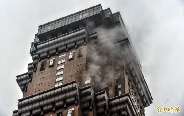 高雄長谷世貿大樓今天下午出現煙狀的雲霧,讓人誤以為是火警。(記者張忠義攝)