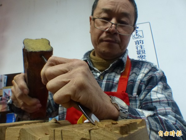 金門木匠師傅胡青年浸淫雕刻工藝35年,對於樟木紋理十分嫻熟。(記者吳正庭攝)