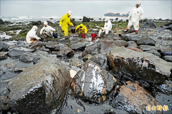 貨櫃輪「德翔台北」斷成兩截,重油污染北海岸,工作人員正忙著清理。(記者林正堃攝)