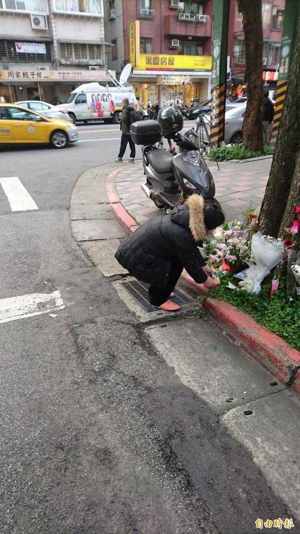 一位太太強忍腿部不適,前來案發現場獻花。(記者游承霖攝)
