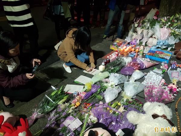 台北內湖今發生女童遭砍殺案,晚間許多民眾自發性到案發地點獻花,不少民眾紛紛在筆記本上,寫下對女童祝福的話語。(記者錢利忠攝)