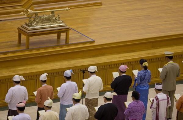 包括翁山蘇姬在內的18名內閣成員,身穿緬甸傳統服飾,在國會大廳宣誓就職。(美聯社)