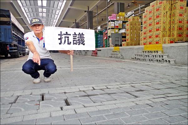 水果業者李志榮表示,每次開車到果菜市場採購,卻因地磚不平車輛震動造成水果撞傷,損失很大。(記者王善嬿攝)
