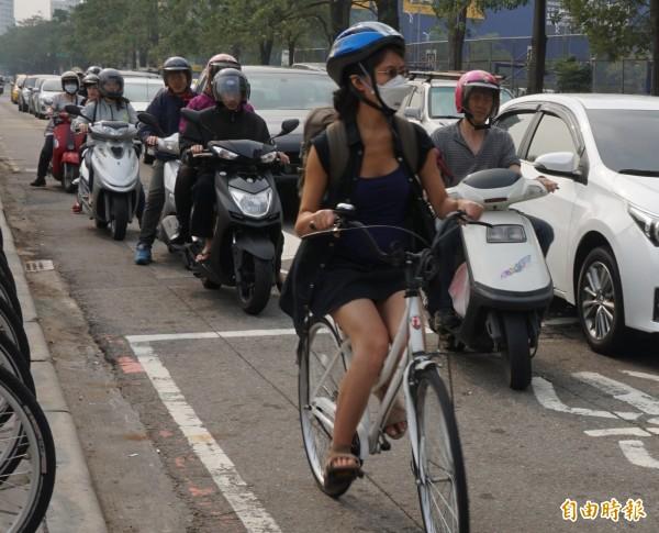 空氣污染嚴重,機車騎士、騎單車美眉和逛街民紛紛戴上口罩防護。(記者蔡淑媛攝)